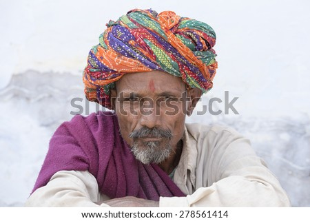 PUSHKAR, INDIA - OCTOBER 25, 2014: Unidentified Indian man, sits on the ghat along the sacred Sarovar lake. Pushkar - famous worship place in India