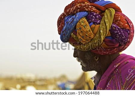 PUSHKAR, RAJASTHAN, INDIA - NOV 22, 2011: Rajasthani wears his colorful turban at the desert of Thar during the annual Camel Trade Fair. - stock photo