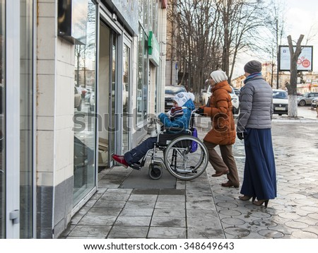 Pushkino, Russia, on December 8, 2015. Moskovsky Avenue. Women with the disabled person in a chair come into shopping center