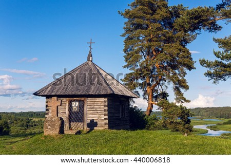 Pushkinskiye Gory, Russia - June 5 : Wooden chapel and stone cross on the top of Savkin hill. Birthday of the great writer Alexander Pushkin , on June 5, 2016.