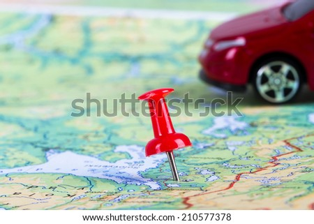 Pushpin and small, toy car on map for travel concept. - stock photo
