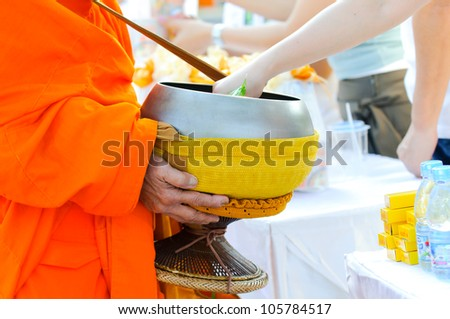 put food offerings in a Buddhist monk's alms bowl, thailand