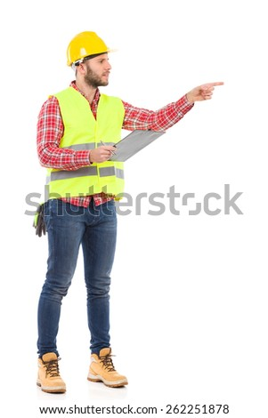Put it there. Manual worker in yellow helmet and lime vest holding a clipboard and pointing. Full length studio shot isolated on white.