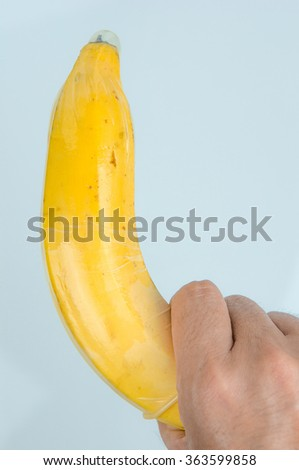 Put on condom with banana for birth control and prevent sexual transmitted disease - stock photo