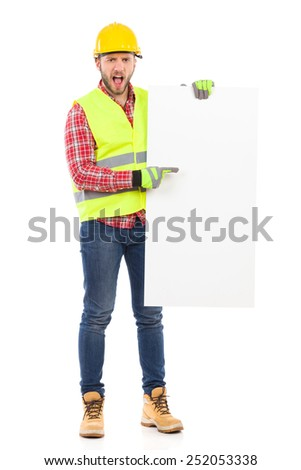 Put something on this placard. Manual worker in yellow helmet and reflective waistcoat holding white placard and pointing. Full length studio shot isolated on white. - stock photo