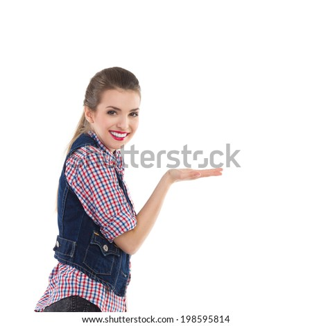 Put your product on my hand. Beautiful smiling girl showing something on the hand. Waist up studio shot isolated on white. - stock photo