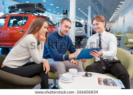 Put your sign on it. Selective focus on young smiling couple signing a contract in clipboard given by the sales consultant with new vehicles on the background