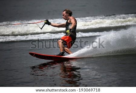 PUTRAJAYA, MALAYSIA - APRIL 26, 2014: Jarno de Lacy of New Zealand rides the waves at the Slalom Open event at the Putrajaya Nautique Ski & Wake Championship 2014. - stock photo