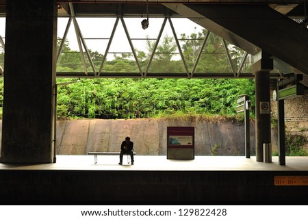 PUTRAJAYA, MALAYSIA - DECEMBER 24:A passenger waits for the next train to Kuala Lumpur International Airport (KLIA) on Dec. 24, 2011 in Putrajaya. The services connecting Kuala Lumpur and the airport. - stock photo