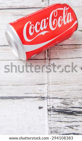 PUTRAJAYA, MALAYSIA - JULY 5TH, 2015. Coca Cola can on weathered wood. Coca Cola drinks are produced and manufactured by The Coca-Cola Company, an American multinational beverage corporation.