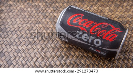 PUTRAJAYA, MALAYSIA - JUNE 28TH, 2015. Coca Cola Zero on wicker background. Coca Cola drinks are produced and manufactured by The Coca-Cola Company, an American multinational beverage corporation.