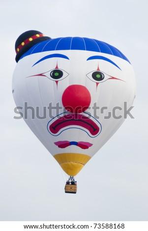 PUTRAJAYA, MALAYSIA-MAR 19:Clown face balloon from Belgium in flight at the 3rd Putrajaya International Hot Air Balloon Fiesta Mar 19, 2011 in Putrajaya.27 International balloonists in this year event - stock photo