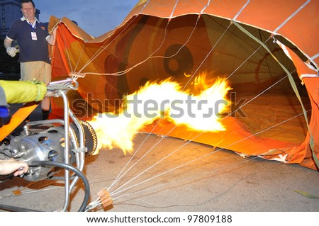 PUTRAJAYA, MALAYSIA-MAR 15:Crew members release flame into the balloon at the 4th Putrajaya International Hot Air Balloon Fiesta Mar 15, 2012 Putrajaya. The burner uses propane gas to heat the air. - stock photo