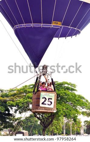 PUTRAJAYA, MALAYSIA-MAR 17: Hot air balloon bring up visitors flight on sky at the 4th Putrajaya International Hot Air Balloon Fiesta Mar 17, 2012 Putrajaya. - stock photo