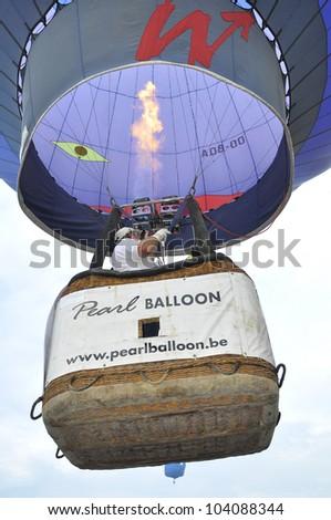 PUTRAJAYA, MALAYSIA-MAR 15:Unidentified visitors in balloon basket going fly on sky at the 4th Putrajaya International Hot Air Balloon Fiesta on Mar 15, 2012 Putrajaya, Malaysia. - stock photo