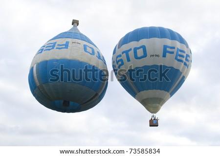 PUTRAJAYA, MALAYSIA-MAR 20:Unique Festo Upside balloon in flight at the 3rd Putrajaya International Hot Air Balloon Fiesta Mar 20, 2011 in Putrajaya.7 special shape balloon participate this year event - stock photo