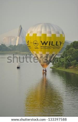 PUTRAJAYA, MALAYSIA - MARCH 30: A balloonist demonstrates his skills by flying his balloon on the surface of the lake during 5th Putrajaya Hot Air Balloon Fiesta at Putrajaya on March 30, 2013. - stock photo