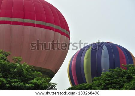PUTRAJAYA, MALAYSIA - MARCH 29:Two hot air balloons are fully inflated during 5th Putrajaya International Hot Air Balloon Fiesta on March 29, 2013 at Presint 2, Putrajaya. - stock photo
