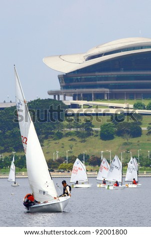 PUTRAJAYA, MALAYSIA - OCT 10: Contestants steer their sailing boats during the Putrajaya Sailing Week on October 10, 2010 in Putrajaya Lake, Malaysia. PICC building landmark is the background building