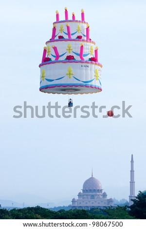 PUTRAJAYA-MARCH 18: Unique Birthday Cake balloon flies over Putra Mosque at the 4th Putrajaya International Hot Air Balloon Fiesta on March 18, 2012 in Putrajaya, Malaysia. - stock photo