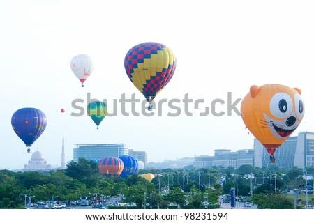 PUTRAJAYA-MARCH 18: Variety of balloons take flight at the 4th Putrajaya International Hot Air Balloon Fiesta on March 18, 2012 in Putrajaya, Malaysia. 24 International Balloonist attended the event. - stock photo