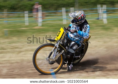 PUTTENHAM, UK - JULY 14: An unnamed rider competing in the Puttenham grasstrack racing event negotiates the circuits bottom corner apex at speed on July 14, 2013 in Puttenham