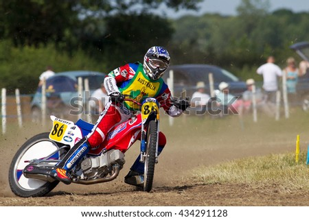 PUTTENHAM, UK - JULY 14: An unnamed rider from Australia takes the bottom corner of the circuit at speed during the Puttenham grasstrack meeting on July 14, 2013 in Puttenham.