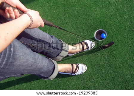 Putting a ball at an adventure golf. - stock photo