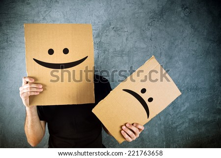 Putting a smiling face on. Man holding cardboard paper with smiley face printed on as happiness and joy concept. - stock photo