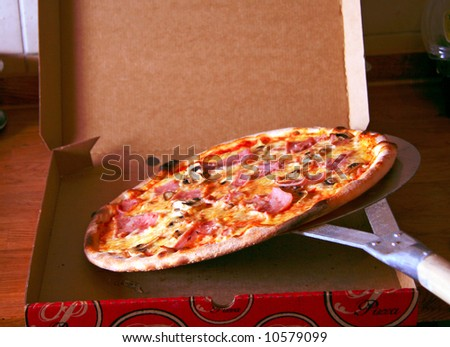 Putting an italian pizza in to the box ready for delivery - stock photo