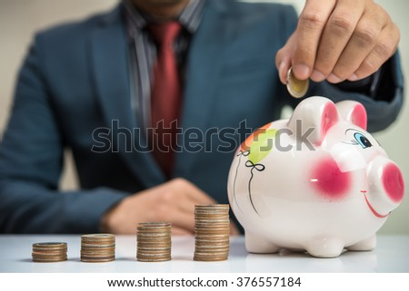 putting coin into a piggy bank  - stock photo