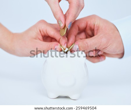 Putting coin into the piggy bank, isolated o white background - stock photo