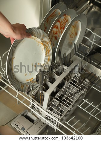 Putting dirty plates in the dishwasher after dinner - stock photo