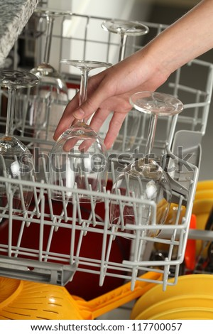 Putting glasses into dishwasher, cleaning a kitchen