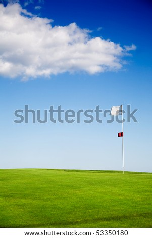 Putting green against blue sky with clouds - stock photo