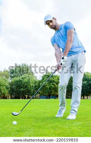 Putting green. Full length of young man in sports clothing playing golf while standing on green  - stock photo