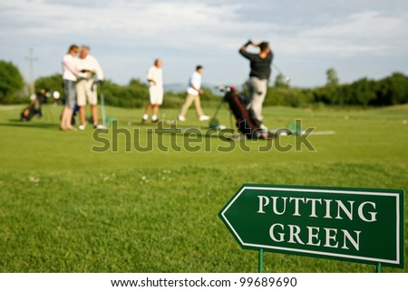 Putting green guidance board in the foreground and golf players out of focus on the background. - stock photo