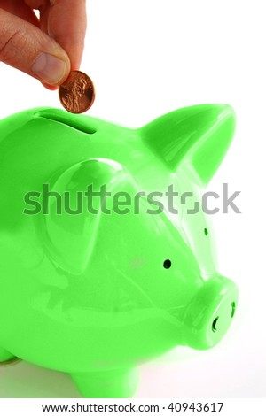 Putting money into the green piggy bank - stock photo