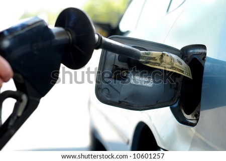 Putting money into the tank (high gas prices) - stock photo