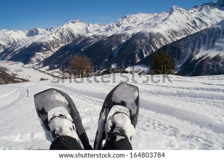 Putting my feet up to enjoy the view on a snowshoe hike to the Galmihornhutte in Gomstal, Wallis, Switzerland. - stock photo