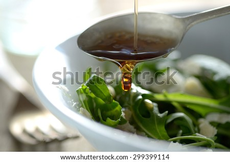 Putting oil on the salad with fork in the background - stock photo