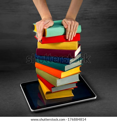 putting or download colorful books to the tablet - stock photo