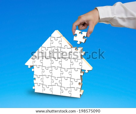 Putting puzzle in house shape blue background - stock photo