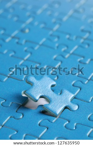 Putting the last piece of puzzle in place - stock photo