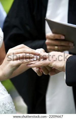 Putting the ring on the groom during a wedding ceremony