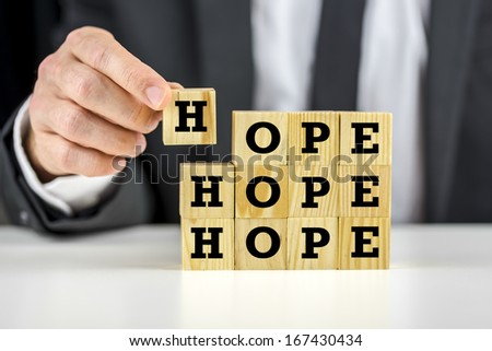 Putting together wooden cubes with letters on them creating word Hope. - stock photo