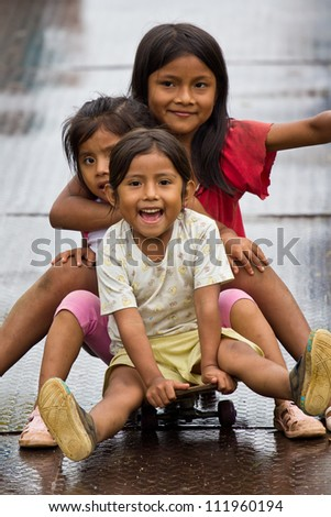 PUYO, ECUADOR - JANUARY 7: Unidentified Amazonian Quechua girls have fun on January 7, 2012 in Puyo, Ecuador. Quechua are the largest South American ethnic group but few live in the Amazon lowlands. - stock photo