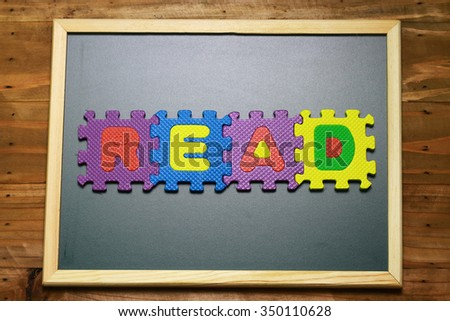 Puzzle block letters.colourful.word read on wood background