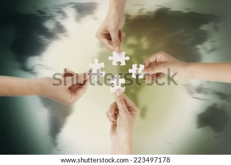 puzzle in hands isolated over the world background - stock photo