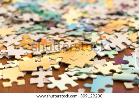 Puzzle on wooden background, depth of field - stock photo